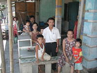 Extended family in front of their traditional Vietnamese home.
